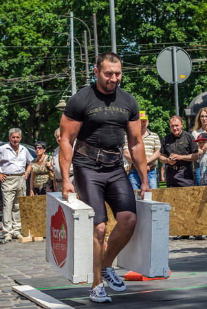 severity: LVIV, UKRAINE - JUNE 2016: Strongman with a large inflated metal body carries heavy suitcases