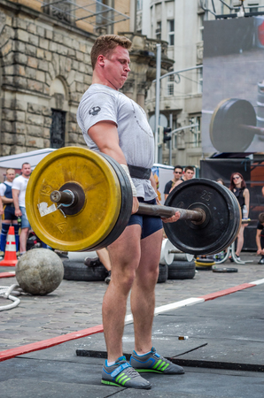 profesional: LVIV, UKRAINE - JUNE 2016: Strong bodybuilder athlete with a beautiful body inflated to lift heavy barbell on a city street