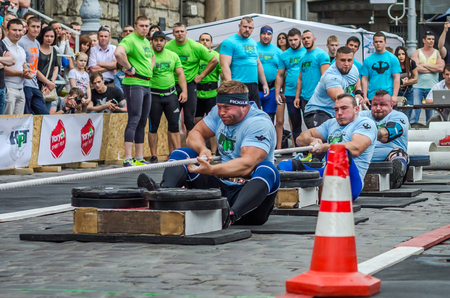 strongman: LVIV, UKRAINE - JUNE 2016: Strong athletes bodybuilders strongman with beautiful bodies and pumped huge muscles competing in a tug of war on the street