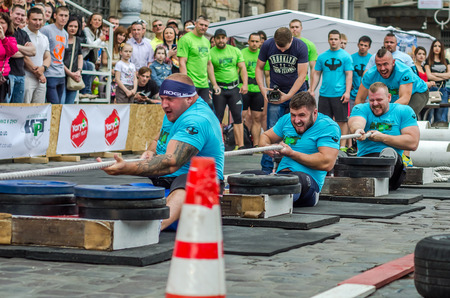 severity: LVIV, UKRAINE - JUNE 2016: Strong athletes bodybuilders strongman with beautiful bodies and pumped huge muscles competing in a tug of war on the street