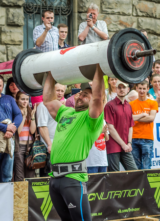 strongman: LVIV, UKRAINE - JUNE 2016: Strong athlete bodybuilder strongman inflated with a beautiful body to lift heavy barbell on the street