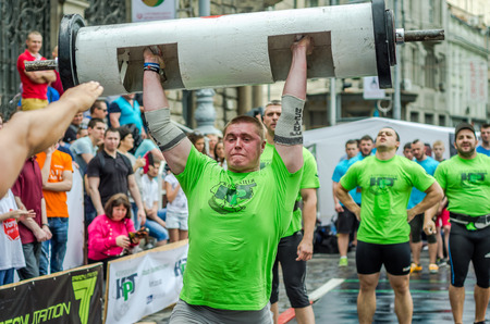 severity: LVIV, UKRAINE - JUNE 2016: Strong athlete bodybuilder strongman inflated with a beautiful body to lift heavy barbell on the street