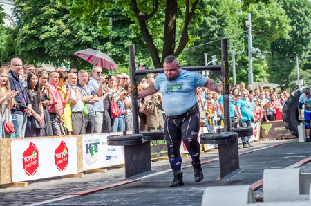 LVIV, UKRAINE - JUNE 2016: Athlete bodybuilder strongman with strong body has an enormous metal structure with pancakes with rod on a city street Editorial