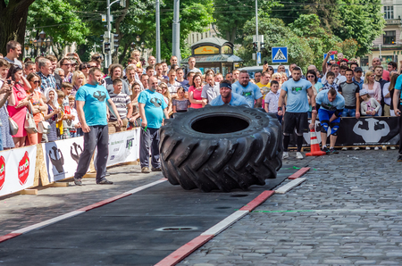 profesional: LVIV, UKRAINE - JUNE 2016: Athlete bodybuilder strongman with strong body pushes a huge turning the wheel of a truck tire
