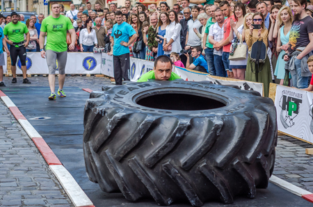 strongman: LVIV, UKRAINE - JUNE 2016: Athlete bodybuilder strongman with strong body pushes a huge turning the wheel of a truck tire