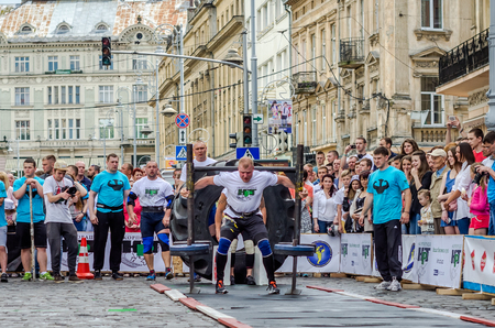 strongman: LVIV, UKRAINE - JUNE 2016: Athlete bodybuilder strongman with strong body has an enormous metal structure with pancakes with rod on a city street Editorial
