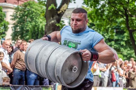 severity: LVIV, UKRAINE - JUNE 2016: Athlete bodybuilder strongman with strong body has an enormous metal barrel with beer