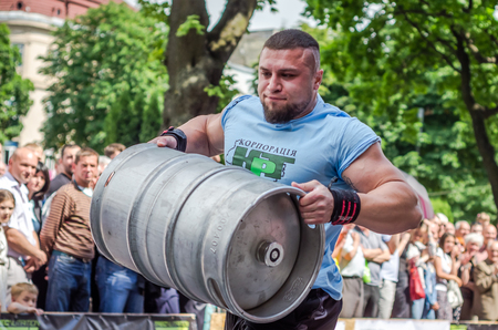 LVIV, UKRAINE - JUNE 2016: Athlete bodybuilder strongman with strong body has an enormous metal barrel with beer