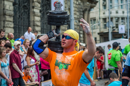 LVIV, UKRAINE - JUNE 2016: Strongman athlete with athletic inflated body lifts the heavy dumbbell on a city street
