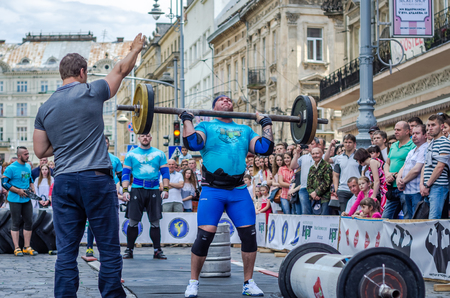 strongman: LVIV, UKRAINE - JUNE 2016: Athlete strongman inflated with athletic body lifting heavy barbell on a city street