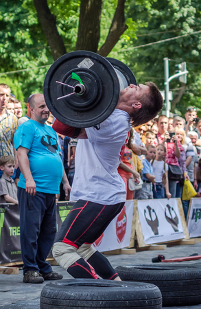 profesional: LVIV, UKRAINE - JUNE 2016: Athlete strongman inflated with athletic body lifting heavy barbell on a city street