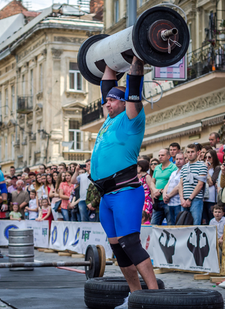 severity: LVIV, UKRAINE - JUNE 2016: Athlete strongman inflated with athletic body lifting heavy barbell on a city street