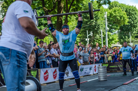 profesional: LVIV, UKRAINE - JUNE 2016: Strong athlete bodybuilder strongman lifts a heavy barbell in front of the audience on a city street