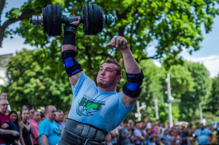 strongman: LVIV, UKRAINE - JUNE 2016: Strong athlete bodybuilder strongman lifts heavy dumbbell in front of the audience on a city street Editorial