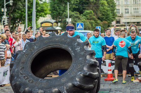 LVIV, UKRAINE - JUNE 2016: Strong bodybuilder athlete, the athlete rolls the wheel of a huge black Goodyear from the truck on the street in front of the amazed public