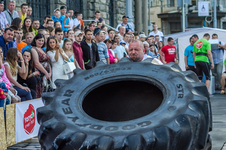 profesional: LVIV, UKRAINE - JUNE 2016: Strong bodybuilder athlete, the athlete rolls the wheel of a huge black Goodyear from the truck on the street in front of the amazed public