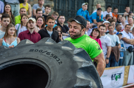 severity: LVIV, UKRAINE - JUNE 2016: Strong bodybuilder athlete, the athlete rolls the wheel of a huge black Goodyear from the truck on the street in front of the amazed public