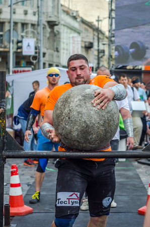 LVIV, UKRAINE - JUNE 2016: Strong bodybuilder strongman lifts a huge heavy stone ball made of marble and throws it over the bar on the street under the eyes of stunned spectators Editorial
