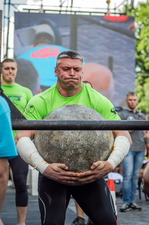 profesional: LVIV, UKRAINE - JUNE 2016: Strong bodybuilder strongman lifts a huge heavy stone ball made of marble and throws it over the bar on the street under the eyes of stunned spectators Editorial