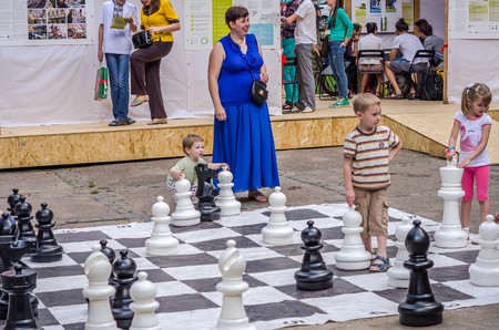 LVIV, 우크라이나 - 6 월 2016 : 어린 자녀, 미래 grandmasters 야외 거 대 한 인물을 운동 체스 보드 체스에 재생