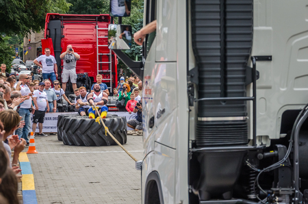 profesional: LVIV, UKRAINE - JULY 2016: Strong athlete strongman pulling a rope truck sitting with a partner is not huge tires