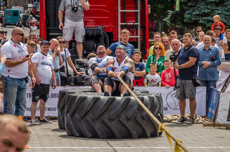 strongman: LVIV, UKRAINE - JULY 2016: Strong athlete strongman pulling a rope truck sitting with a partner is not huge tires