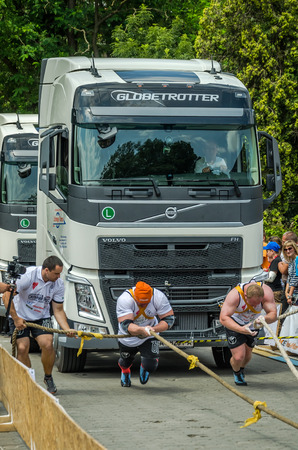 profesional: LVIV, UKRAINE - JULY 2016: Two strong athlete bodybuilder strongman pulling with ropes two huge truck in front of enthusiastic audiences