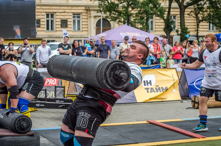 profesional: LVIV, UKRAINE - JULY 2016: Strong athlete bodybuilder pumped strongman with a heavy body raises the bar in front of a pack of enthusiastic spectators on the street on a sunny day