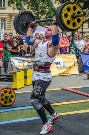 LVIV, UKRAINE - JULY 2016: Strong athlete bodybuilder pumped strongman with a heavy body raises the bar in front of a pack of enthusiastic spectators on the street on a sunny day