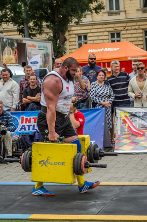 severity: LVIV, UKRAINE - JULY 2016: Mighty strong athlete bodybuilder strongman carries heavy iron suitcases on the street in front of enthusiastic spectators
