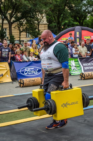 profesional: LVIV, UKRAINE - JULY 2016: Mighty strong athlete bodybuilder strongman carries heavy iron suitcases on the street in front of enthusiastic spectators