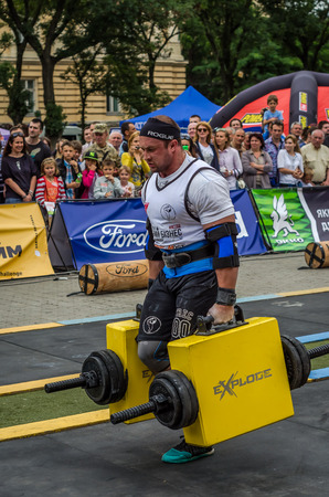 strongman: LVIV, UKRAINE - JULY 2016: Mighty strong athlete bodybuilder strongman carries heavy iron suitcases on the street in front of enthusiastic spectators