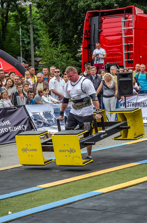 severity: LVIV, UKRAINE - JULY 2016: Strong athlete bodybuilder strongman carries heavy metal design competitions World Strongest Team before enthusiastic audiences