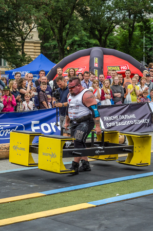 profesional: LVIV, UKRAINE - JULY 2016: Strong athlete bodybuilder strongman carries heavy metal design competitions World Strongest Team before enthusiastic audiences