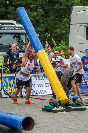 the strongest: LVIV, UKRAINE - JULY 2016: Strong athlete bodybuilder strongman carries heavy metal design competitions World Strongest Team before enthusiastic audiences