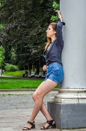 Young cute girl with long hair in a shirt and denim shorts walking in the park in Lviv Striysky sunny summer day posing near the columns at the entrance