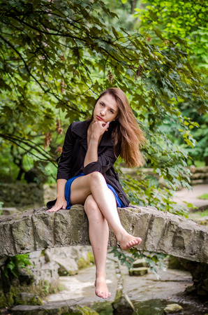 Young charming girl the teenager with long hair walking in the park in Lviv Striysky hot sunny summer day in the beautiful nature and green leaves sitting on the historic stone bridge over a stream