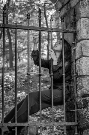 ancient prison: Young charming woman with long hair offender, sits behind bars in an ancient stone prison prisoner and looks pityingly through steel bars begging for freedom
