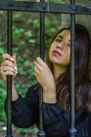 woman prison: Young charming woman with long hair offender, sits behind bars in an ancient stone prison prisoner and looks pityingly through steel bars begging for freedom