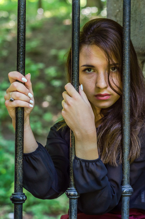 Young charming teenager girl with long dark hair sitting behind bars in a prison