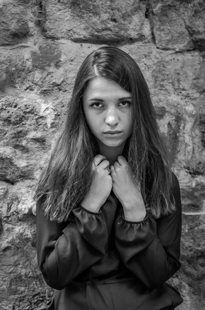 pathetic: Young charming teenager girl with long dark hair standing with a sad expression on his face sad and pathetic emotions in Striysky Park in Lviv Stock Photo
