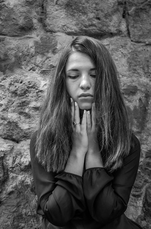 pathetic: Young charming teenager girl with long dark hair standing near the ruins of the ancient castle fortress with a sad expression on his face sad and pathetic emotions in Striysky Park in Lviv