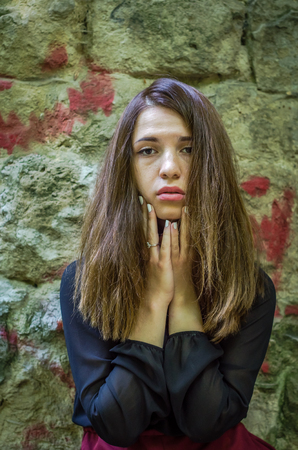 Young charming teenager girl with long dark hair standing with a sad expression on his face sad and pathetic emotions in Striysky Park in Lviv Stock Photo