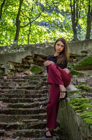 fashion clothing: Young charming teenager girl with long dark hair is a graceful gait destroyed by an ancient staircase the steps in Striysky Park in Lviv
