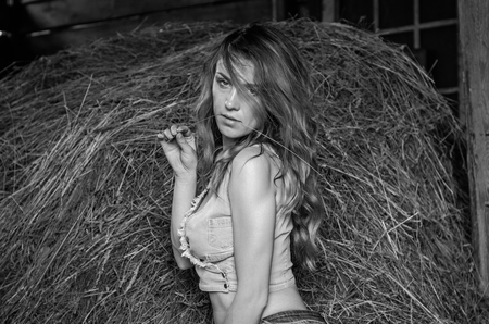 Young charming blonde girl with long hair in a barn on a farm near a haystack in the countryside with alluring eyes is wearing a denim top and short shorts sexy
