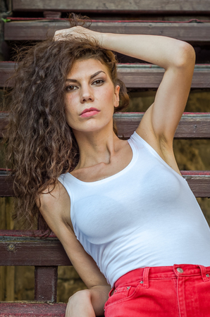 warm shirt: Young charming leggy girl with curly hair in a white shirt and red shorts sitting on the wooden stairs near the fortress in Lviv during a walk on a warm summer sunny day Stock Photo