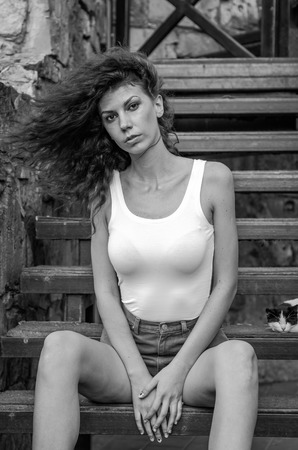 leggy girl: Young charming leggy girl with curly hair in a white shirt and red shorts sitting on the wooden stairs near the fortress in Lviv during a walk on a warm summer sunny day Stock Photo