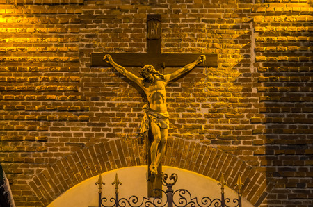 Statue of Jesus Christ crucifixion on a brick wall background
