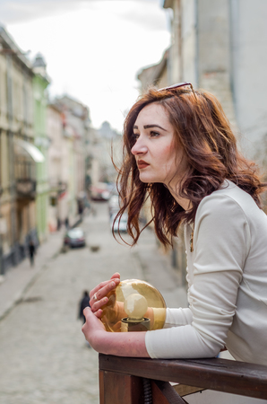 Young beautiful girl hugging a round luminaire while walking the streets of the old city of Lviv