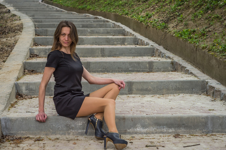 Young charming sexy girl with long hair in a black dress strolls in the park on the steps